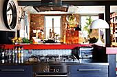 Blaue Küchenzeile mit Gasherd und Edelstahl-Arbeitsplatte vor Durchreiche