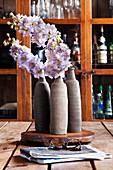 Drei Vasen mit Blumen, im Hintergrund Geschirrschrank