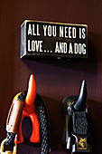 Funny wall hooks in the shape of a dog's tail with a message above