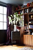 Vase mit Blütenzweigen auf Schubladenschränkchen vor Fenster