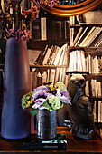 Vases and vintage table lamp in front of a bookshelf