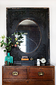 Mirror with black passe-partout frame above a chest of drawers