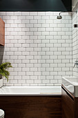 A bathtub in front of a white tiled wall