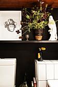 Regal mit Bild, Pflanze und Skulptur im Badezimmer
