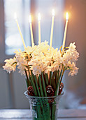 White flowers with cones and candles in a crystal vase