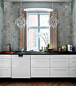 White kitchenette with black worktop, above and chandelier