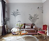 An elegant sofa in front of a wall papered with palm tree wallpaper with a coffee table and an antique chair in a living room