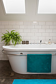 Bathtub with towel rail and indoor fern under skylight in bathroom with white underground tiles