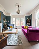 Pinkes Sofa im klassischen Wohnzimmer im Altbau mit Erker