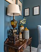 Alte Steingutkrüge und Leuchte auf altem Tischchen vor blauer Wand