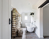 Free-standing bathtub and exposed stone wall in bathroom
