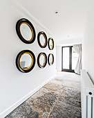 Collection of mirrors on white wall in hallway with stone-flagged floor