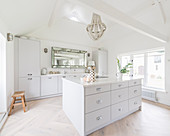 White fitted kitchen with island counter in converted barn