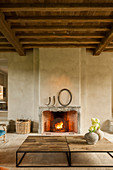Fire in open fireplace in rustic living room