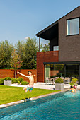 Boy jumping into pool in garden of modern house