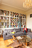 Man in front of bookcase and woman reading on sofa in living room