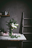 Beautiful glass vase with bunch of whites flowers with leaves on marble tabletop beside dark wall