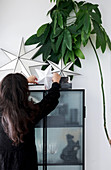 Woman placing paper stars on top of cabinet next to houseplant