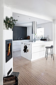 White island counter, wooden floor and wood-burning stove in open-plan kitchen