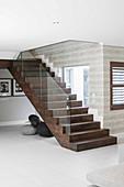 Dark wooden staircase with glass balustrade in modern interior