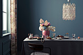 Feminine breakfast table with bouquet and jewelry, designer chandelier above