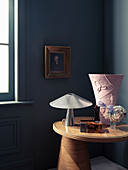 Side table with table lamp and vase in corner of room, portrait on the wall