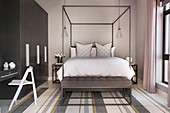 Modern four-poster bed in bedroom in shades of grey