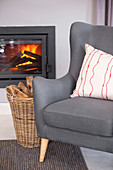 Grey armchair and basket of wood in front of fire in glass-fronted fireplace