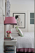 Bed with white bedspread, table lamp with gingham lampshade on bedside table and pictures on walls