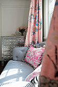 Couch with striped cover and toile-de-jouy cushions in front of antique chest of drawers