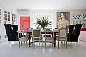 Various chairs and wingback armchairs around dining table and modern artworks on white wall