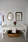 White double washstand below antique mirrors on tiled wall