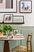 Small dining table and chair next to wall with pictures above wainscoting