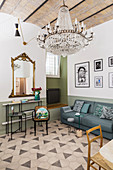 Console table, gilt-framed mirror, sofa and chandelier in living room