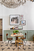 Small dining table and chairs next to wall with pictures above wainscoting