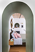 View of double bed through arched doorway