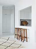 Wooden stool in front of serving hatch between kitchen and dining room