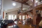 Gallery and wooden beams in open-plan interior on multiple levels