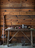 Skis leaning against rustic wooden wall next to buffet of salami, wine and bread