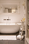 Modern oval bathtub below mirror on wall of shabby-chic bathroom