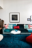 Comfortable sofa with scatter cushions and slender coffee table on blue carpet in living room