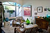 Rattansessel, antik Kommode und moderner Beistelltisch im Wohnzimmer mit Blick auf Balkon