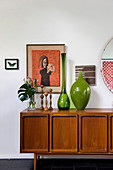 Green glass vases, candlesticks and plants on retro sideboard below artworks on wall