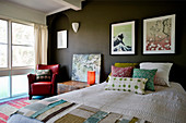 Scatter cushions and fabric samples on bed, bedside table and red leather armchair below pictures on dark wall in bedroom