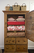Red household textiles in old wooden cabinet with open door