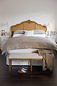 Polsterbank vorm antiken Bett im Schlafzimmer in Braun und Weiß