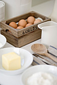 Eggs in small wooden box, baking ingredients and utensils