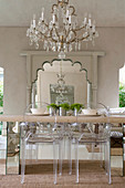 Transparent designer chairs around dining table below chandelier