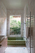Mosaic bathrub below window in Mediterranean bathroom