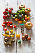 Multicoloured tomatoes on wooden table